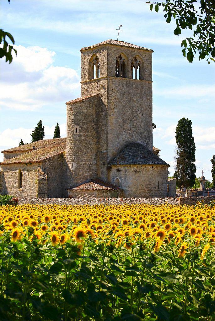 Church in sunflower field near Lacapelle-Cabanac, France