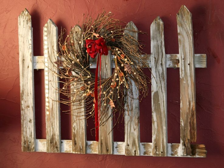 Old picket fence section with wreath.  Great way to repurpose something old!