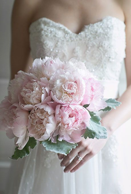 Brides.com: . This classic pale-pink peony bouquet, created by Flowers by Grattoni, a Chicago-based florist, pops thanks to dusty miller around the base.