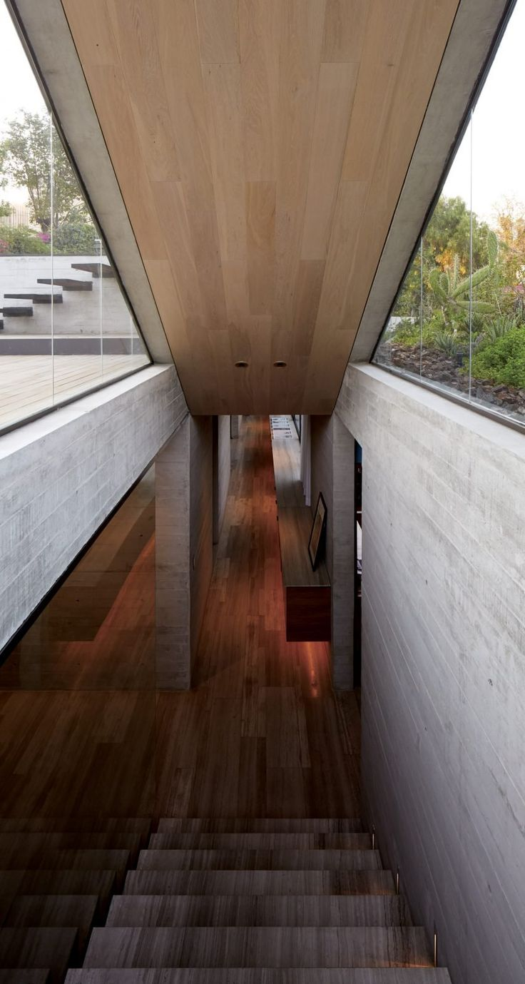 This concrete home shaded by a wooden screen by Chilean architects Felipe Assadi and Francisca Pulido is elevated off the ground