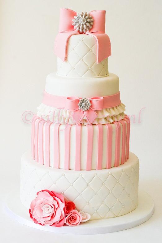 Een hele mooie roze bruidstaart met strikken.