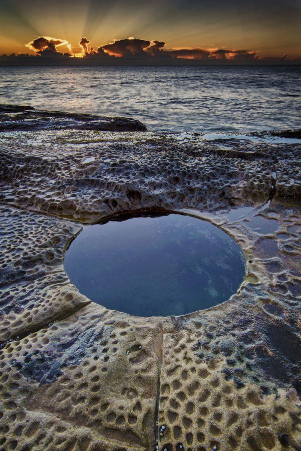 Deep rock hole on the rock shelf north of Curl Curl pool at sunrise. Curl Curl beach, Sydney Australia. by Glenn Crouch