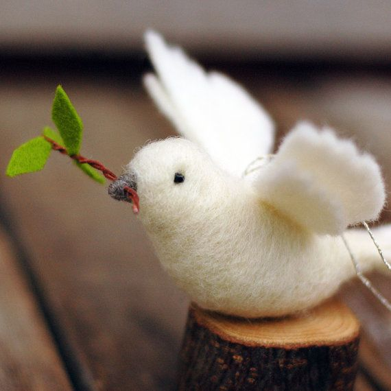 A message of peace for any season~  Our peace doves are needle felted out of white wool. Each bird has black bead eyes, a wrapped grey beak, and a small wire and wool olive branch held in its beak. Birds measure almost 6 inches long and have a gold thread hanger.  We will choose a peace dove ornament in this style for you at the time of shipment. Please expect and allow for the small and delightful variations to be found in handmade items!  -----------------------------  Our felted creations…