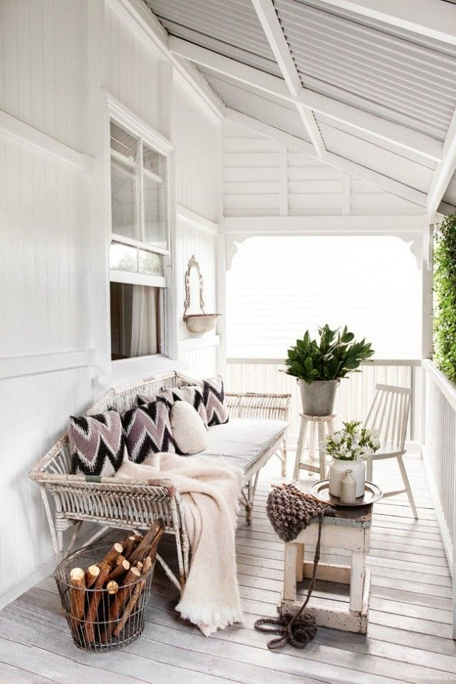 Outdoor living space with vintage white bench, a metal basket, and a white wooden chair