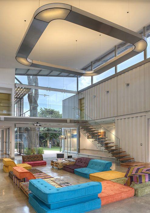 На первом этаже расположена гостиная, кухня со столовой и галерея с работами хозяина. Центральное пространство площадью 95 квадратных метров может периодически выступает в роли комнаты отдыха или же фотостудии. Кухня со столовой сделана из двух соединенных контейнеров. Барная стойка, ножки стола и стулья там выполнены из веток кедра, растущего во дворе дома.