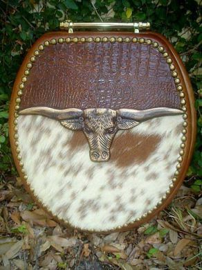 Gorgeous, custom toilet seat accented with a cast iron Longhorn, French natural tacks, cowhide, and alligator embossed leather.
