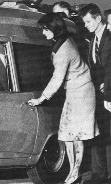 This photo clearly shows the blood-soaked Chez Ninon suit  that Jacqueline Kennedy was wearing when her husband, John F. Kennedy, was assassinated in Dallas on November 22, 1963.