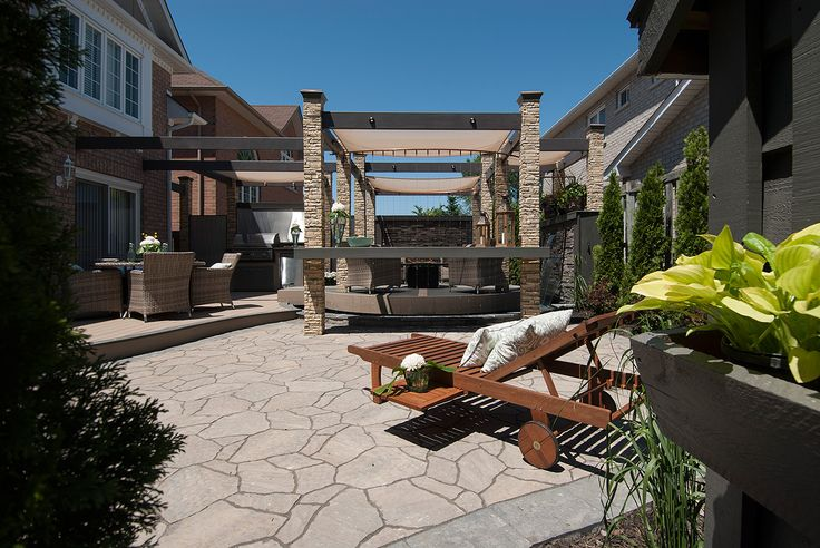 """A large, private interlock stone patio offers generous space to lounge.  From """"Decked Out"""" project """"The Moat Deck"""".  Deck Design by Paul Lafrance Design."""
