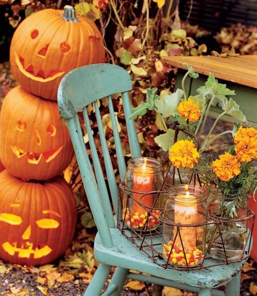 Anchor pillar candles in Mason jars among a bed of candy corn or black and orange jelly beans for a simple and festive Halloween decoration for the tabletop or porch.   - CountryLiving.com