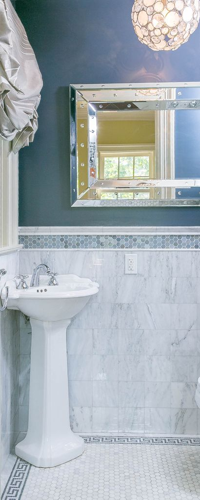 Tiny powder room with blue border tile over marble with greek key and pedestal sink