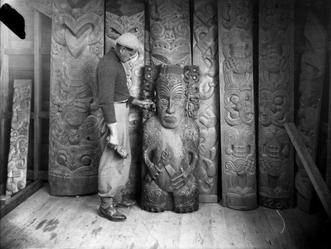 Pine Taiapa standing with items of Maori wood carvings (probably his own work) for the Kahungunu Meeting House in Nuhaka. Photograph taken circa 1940s, by an unidentified photographer.