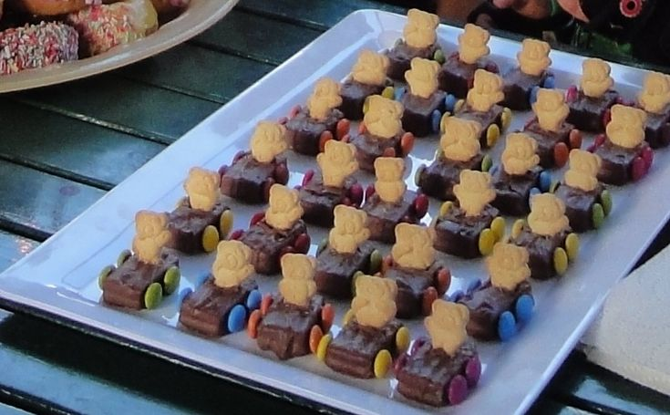 Teddy Grahams in Milky Ways with M&M;'s as wheels (glued on by chocolate)  Such a cute idea!  Maybe put in candy bags as favors......