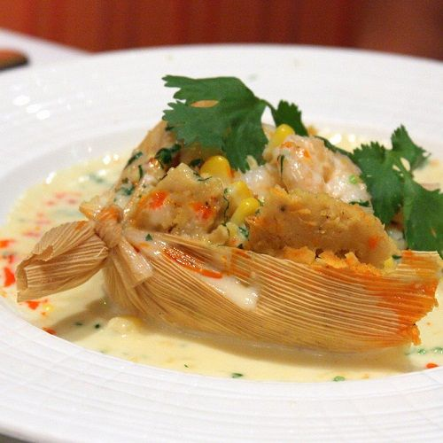 Watch Super-Star Chef Bobby Flay prepare fresh corn tamales with shrimp and roasted garlic — the signature dish at his award-winning flagship restaurant, Mesa Grill, at the 2007 Food & Wine Classic in Aspen. Complete recipe is below the video.  Bobby Flay's Shrimp Tamales Recipe Ingredients Tamales 4 cups fresh Corn Kernels (the corn from about 8 good ears) 1 1/2 cups Water 1 small Onion, coarsely chopped 2 tablespoons Honey 1 tablespoon Kosher Salt 1 teaspoon freshly ground Pepper 1 1/2…