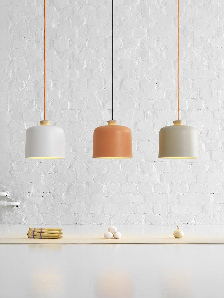 fuse lamp series - note design studio fot E-xt . A soft porcelain pendant lamp accentuated by a wooden pendant holder that together emulate the warm glow created within each cylindrical shade.