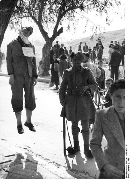 Hung man next to Greek soldier during German occupation, reason unknown, Greece 1943.