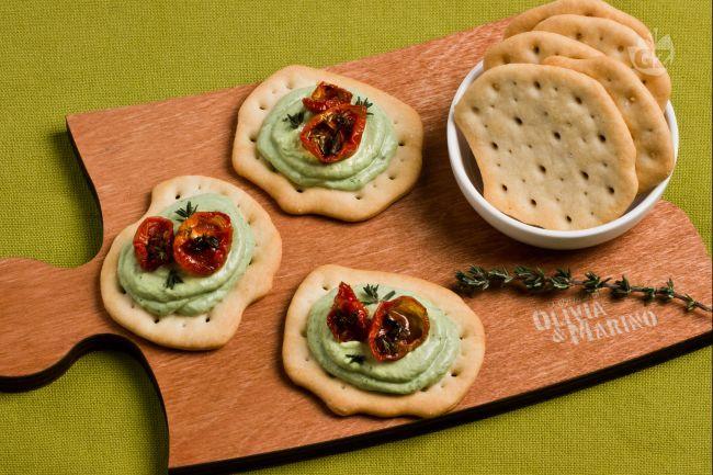 Le schiacciate con crema al basilico sono degli antipasti preparati con una crema di robiola al basilico e guarniti con pomodorini confit.