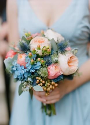 Wedding bouquet with peach peony, blue hydrangea, blue thistle and viburnum berry.