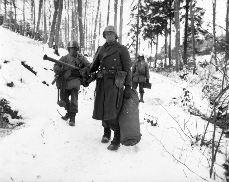 """U.S. Army combat engineers of """"B"""" Company, 101st Engineer Battalion, trudge through the densely wooded Ardennes forest after holding a woodland position all night against a German counter attack during the Battle of the Bulge. Near Wiltz, Diekirch District, Luxembourg. 14 January 1945."""