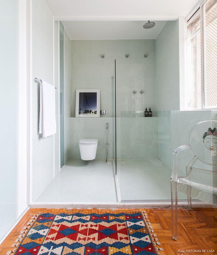 Banheiro amplo com revestimentos de pastilhas brancas, piso de tacos e tapete étnico.