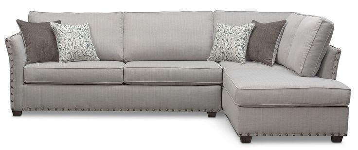 Eternal Excellence. Abundant with classic appeal, the Mckenna sectional makes a grand statement. With its comfortable seating, this furniture features oversized nailhead trim adorning the ever-stylish flared arms. Complemented beautifully with contrasting-colored accent pillows, the soft gray fabric is versatile and will match any décor. Two-piece sectional includes left-facing sofa and right-facing chaise, as shown.