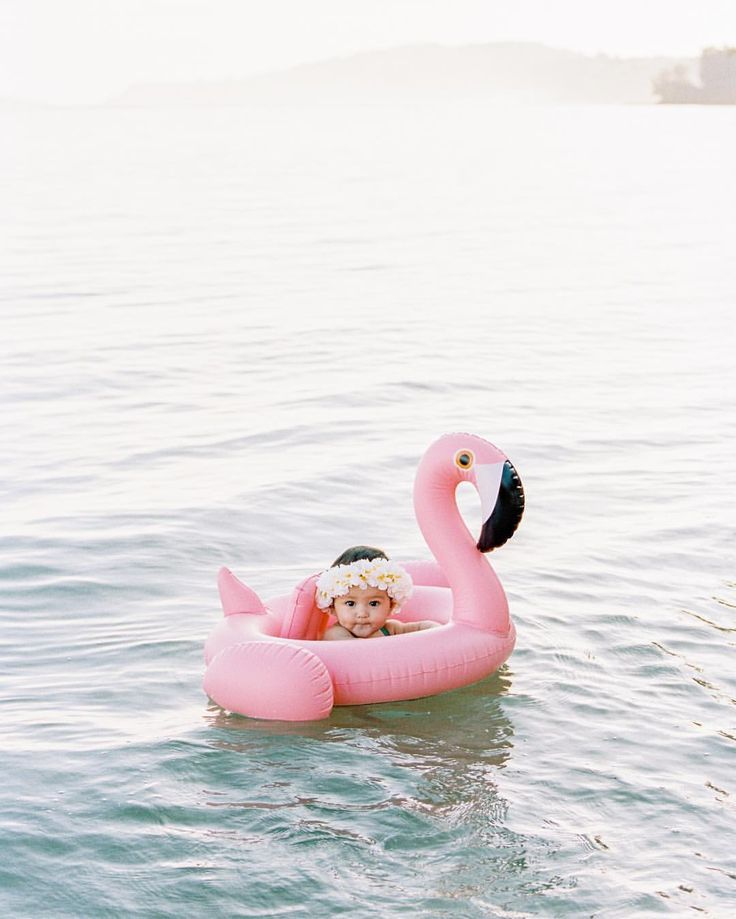Baby girl wearing flower crown in pink flamingo float! Great idea for a beach photo shoot with infant or toddler.
