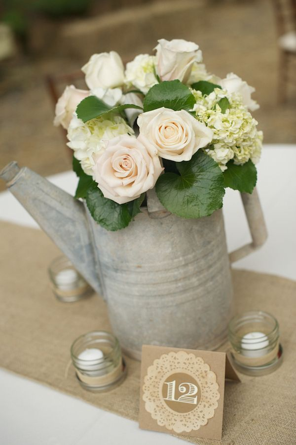 Vintage watering can centerpiece - nice.... Like the candles around it, the stamped/kraft paper table card & the burlap runner as well.