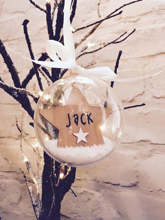 Personnalisé suspendus babiole clair avec étoile en bois personnalisé. La boule est suspendu à un ruban en satin crème et se termine avec de la neige blanche à l'intérieur de la boule. Dans cette liste, vous pouvez choisir 1 babiole ou profitez de notre offre d'achat multiples de 2
