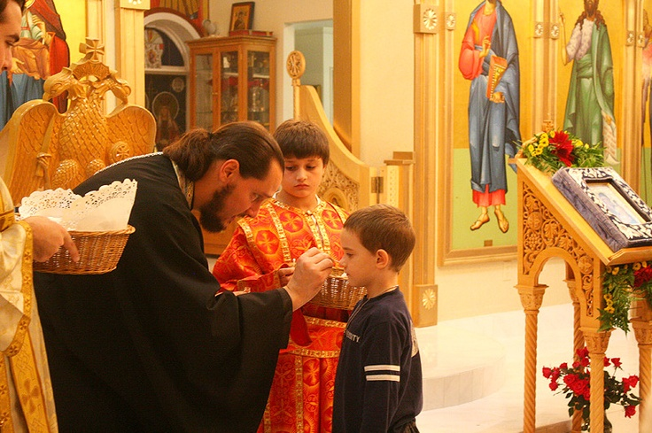 Little boy receiving Holy Communion in an Orthodox church