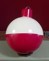 I got this idea from meandering around . . . this is my grandpa's old bowling ball, spray paint red & white, I used the red spray paint can lid and hanger hook end on top!