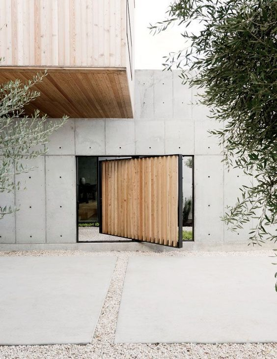 A low concrete wall surrounds the entry courtyard, which leads to a concrete…