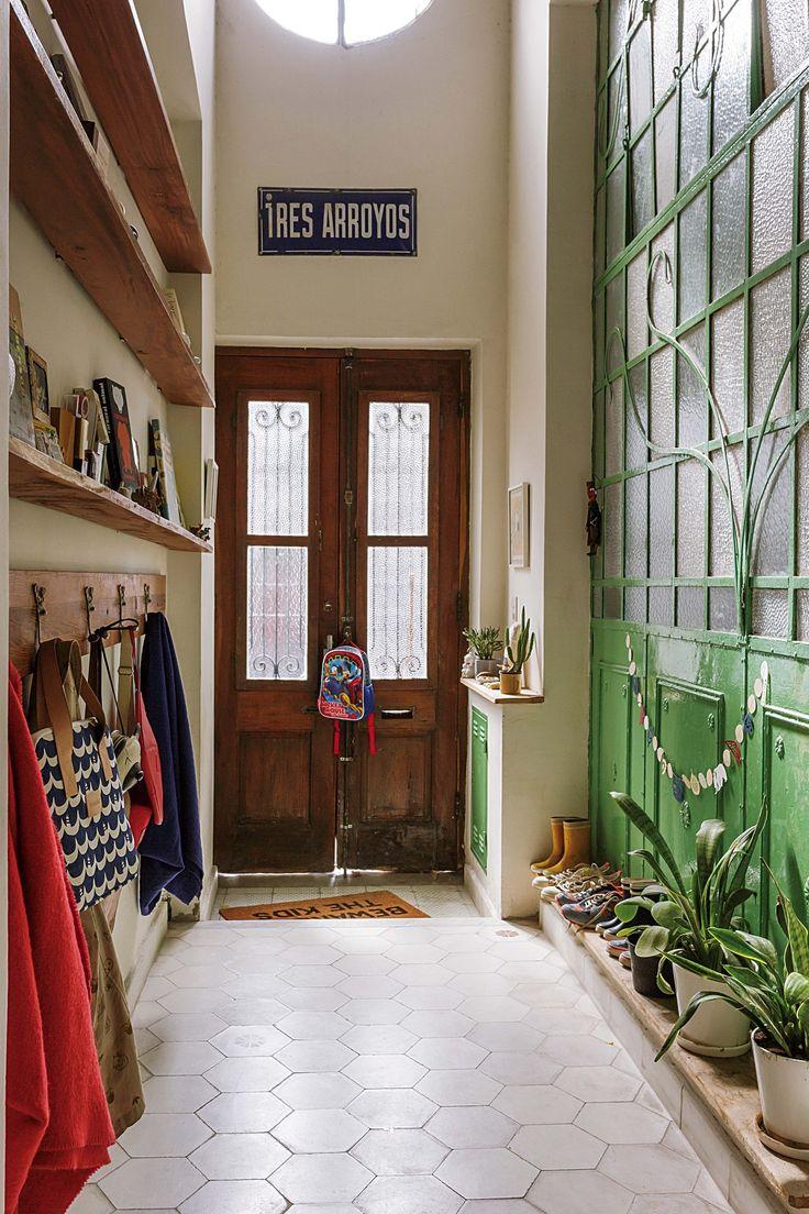 En el recibidor de la casa de la diseñadora Valeria Pesqueira, colores y estímulos en orden, con una fila de macetas y biblioteca angosta con perchero de madera. El piso es de calcáreos grises en forma de panal, de Colacioppo Hnos.