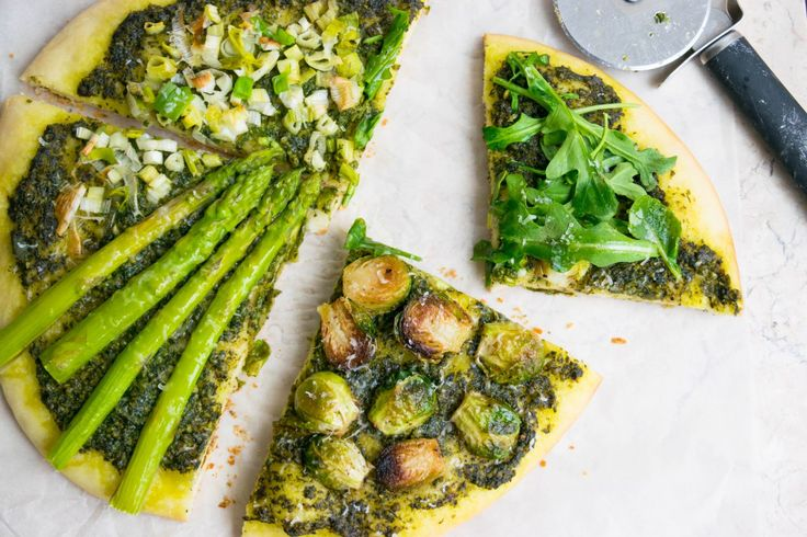 A vegetarian, green pizza with a spinach pea pesto sauce and topped with asparagus, caramelised Brussels sprouts, arugula and Spring onions.