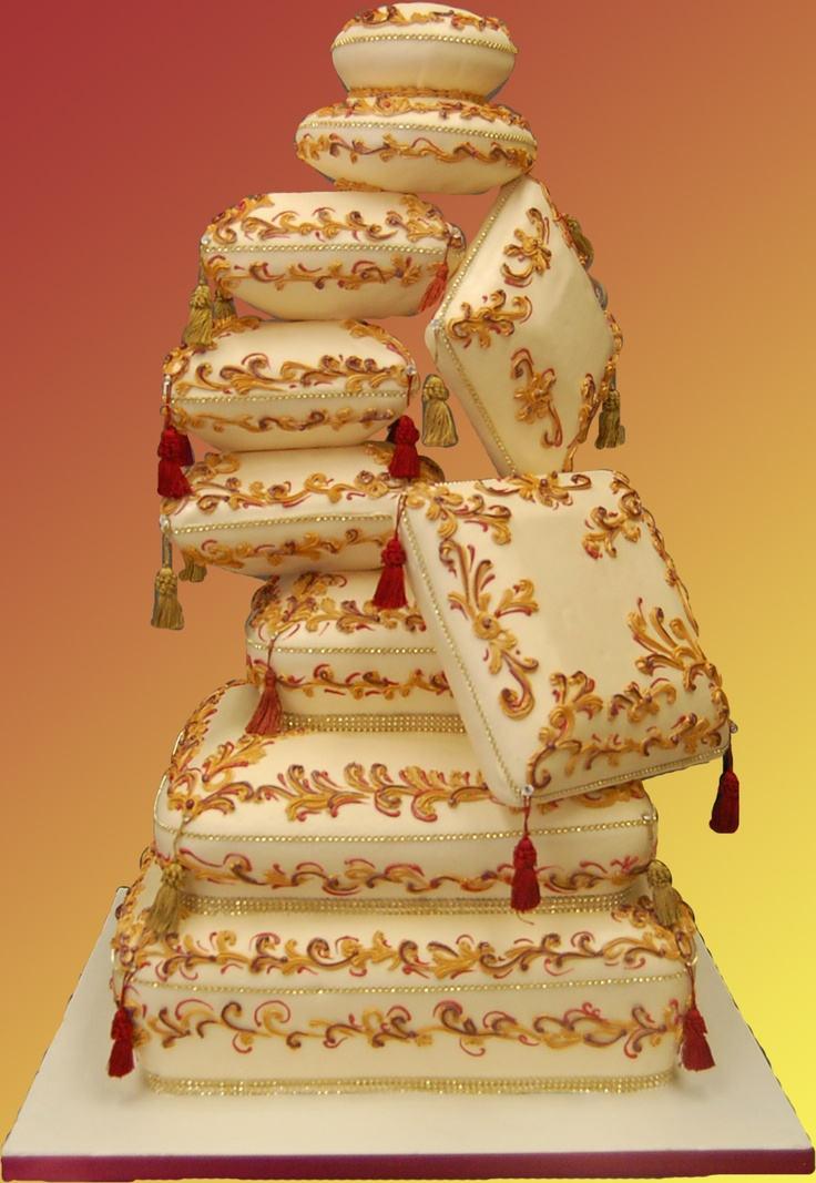 A super unique and interesting wedding cake - sculpted to look like a pile of beautifully decorated pillows.