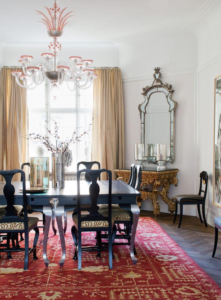 Vid de svarta matsalsbordet med silverben från Bohem sitter gästerna på 1700-talsstolar, klädda i tyg från Oscar & Clothilde. Ovanför det magnifika konsolbordet, 1800-tal, hänger en spegel i senbarock, svensktillverkad av Burchardt Precht. Matta Knut och sidengardiner Walles & Walles. Ljuskronan är från Cenedese i Venedig. / Sköna Hem