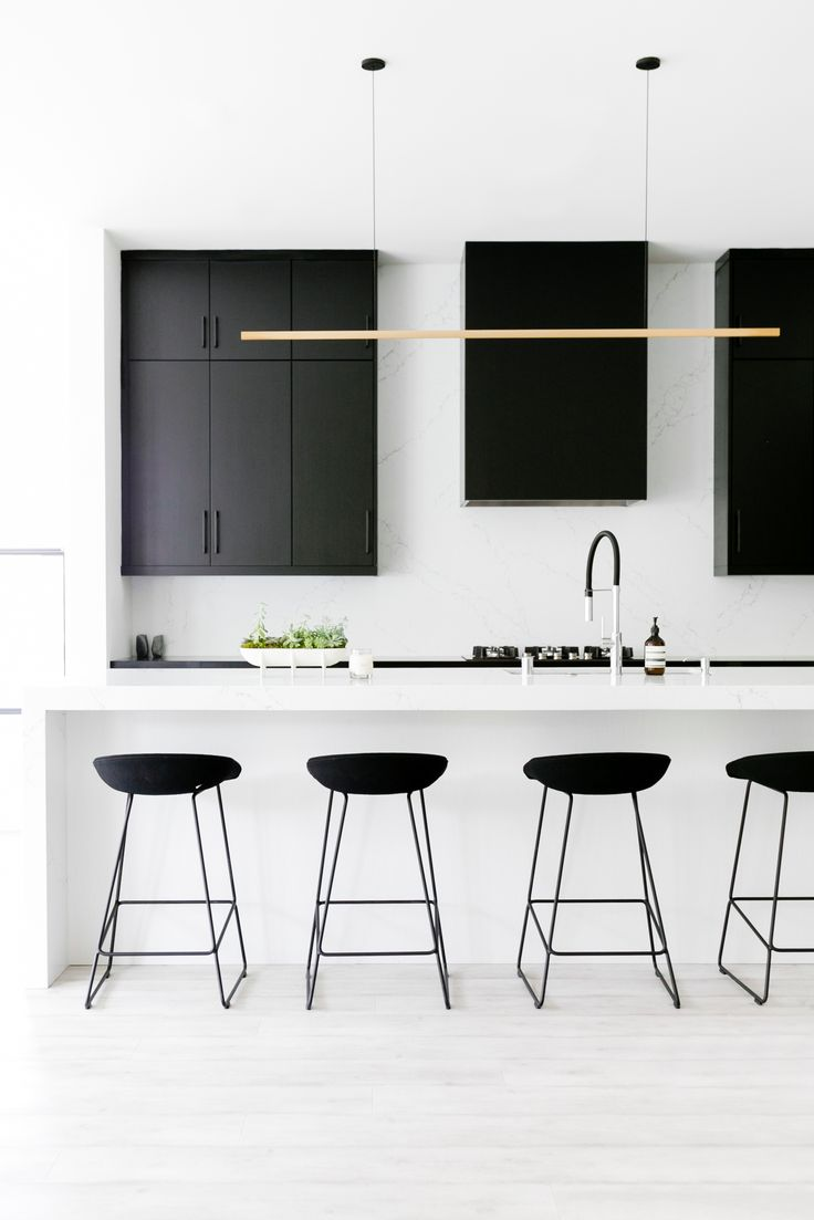 Que tal ambientes minimalistas? O escritório @well_received criou contrastes marcantes entre o branco e preto nesta cozinha, cores que dominam o espaço até mesmo na coifa! A luminária dourada foi uma escolha certeira para completar a decoração, imprimindo elegância e estilo. Foto: Monica Wang.