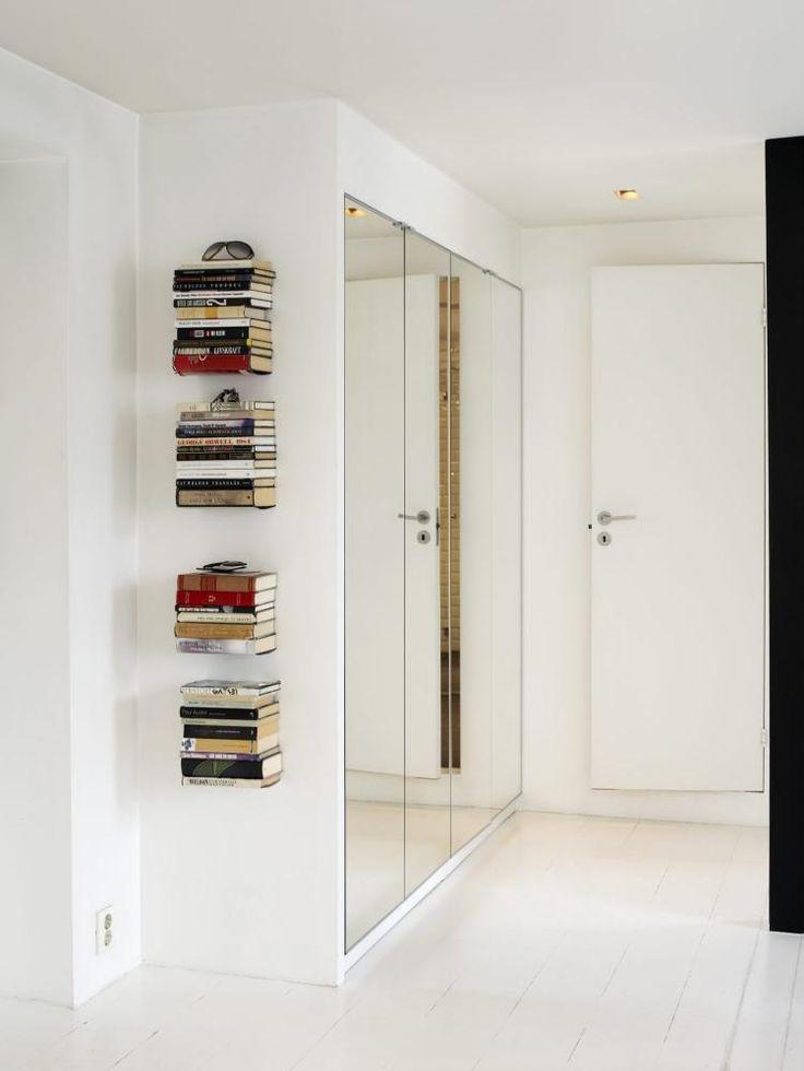 VEGGHENGTE BØKER I GANGEN: Bøkene tres rett på de tynne bokhylleplatene slik at bøkene synes å henge rett på veggen. Oppbevaringsbehovet man har i enhver entré finner sin løsning i speilgarderoben.