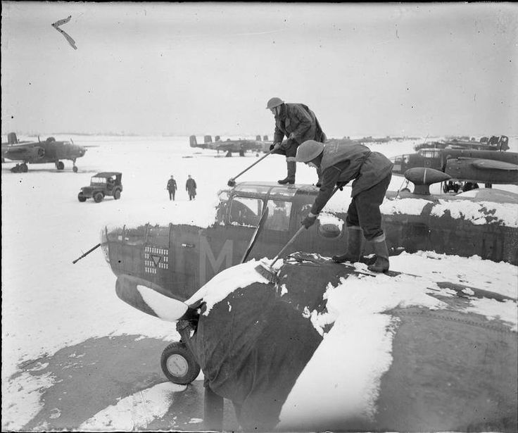 Ground crew sweep snow from a North American Mitchell Mark II of No. 320 (Dutch) Squadron RAF at B58/Melsbroek, Belgium, in preparation for a mission.