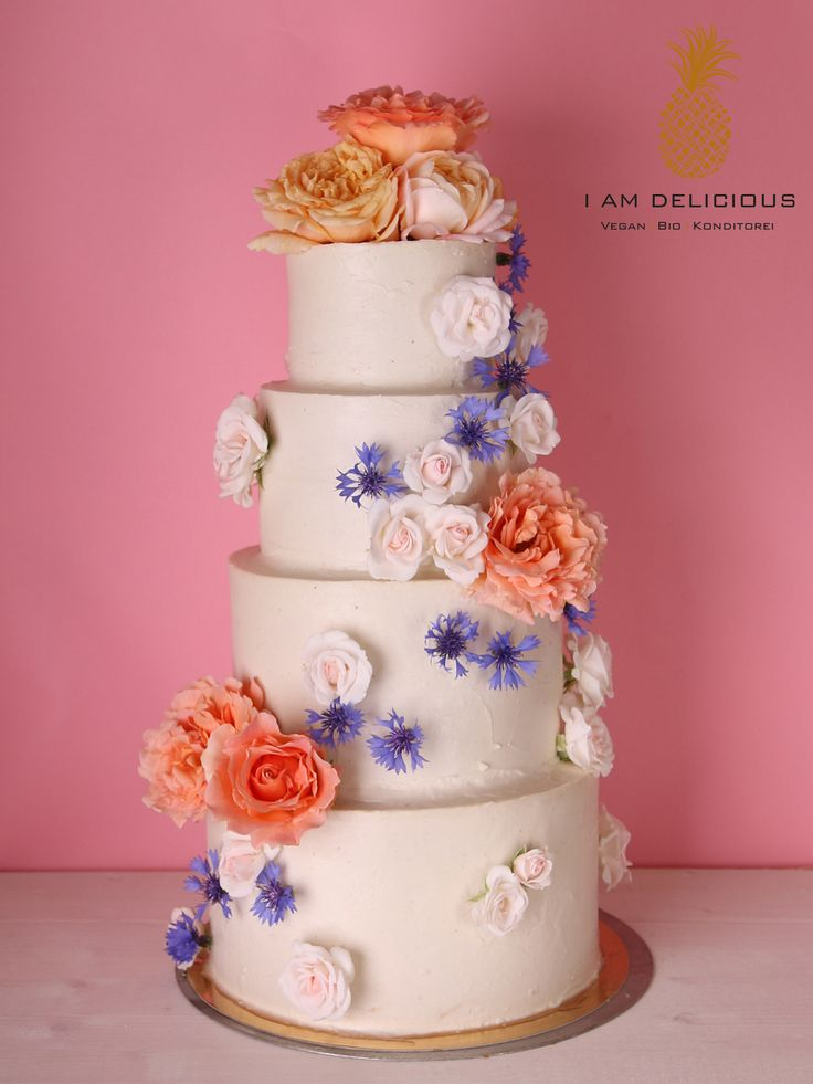 Vegane vierstöckige Hochzeitstorte von I AM Delicious. Eine leckere fruchtig-schokoladige Torte mit wunderschönen Blumen. Innen saftig, schokoladig und außen mit einer fruchtigen, veganen Creme umhüllt.