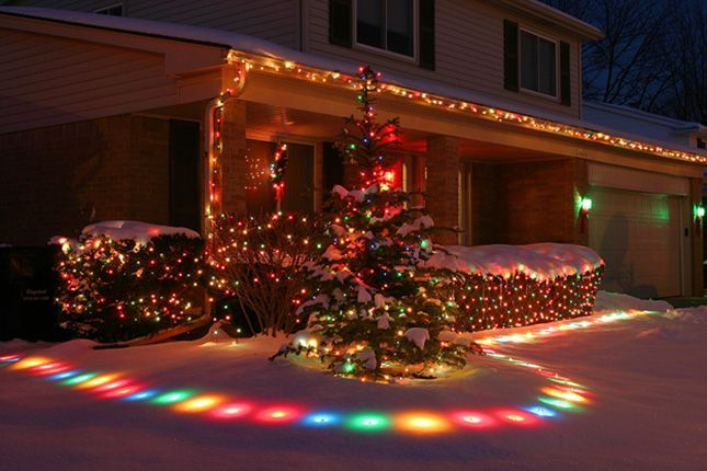Colorful Yard Lights: Who knew lawn lights could look so cool? We love how the technicolor bulbs glow under a foot of snow #outdoorchristmaslights