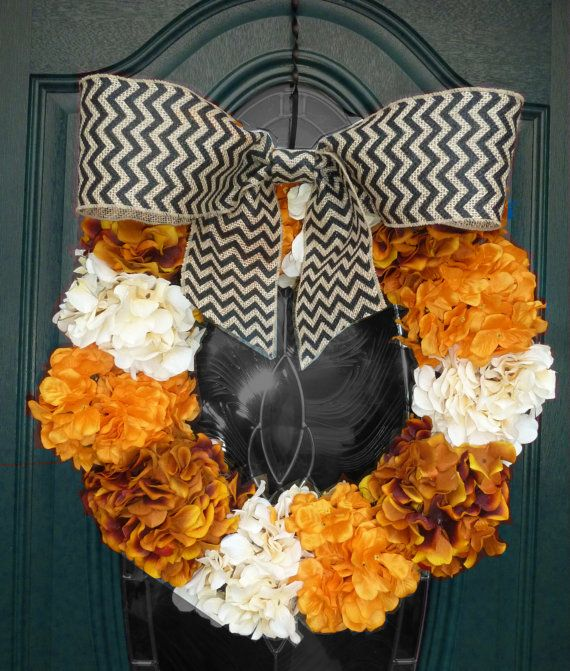 Stylish and elegant fall (and Halloween!)wreath - an original, handmade design! 12 hydrangeas in bursts of autumn colors - orange, burnt orange/brown and cream surround this grapevine wreath.  It is then adorned with a wide, wired, black chevron burlap bow.  Greet your guests in style!
