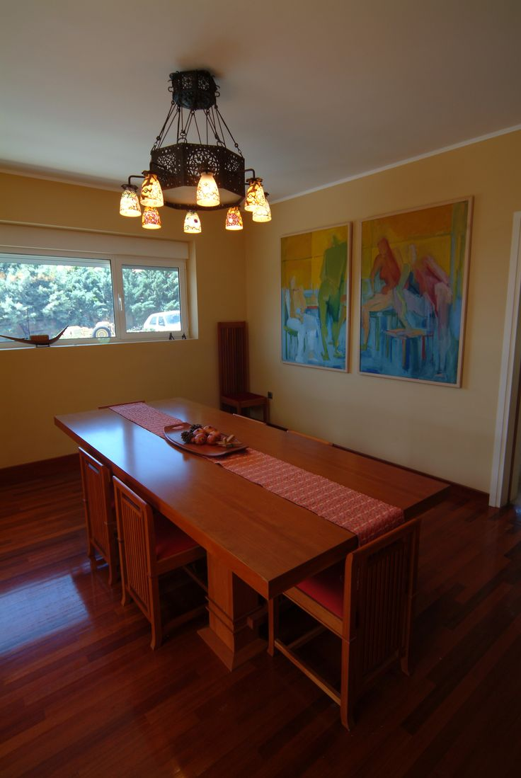 Frank Lloyd Wright dining table and chairs and Egyptian wrought iron chandelier.