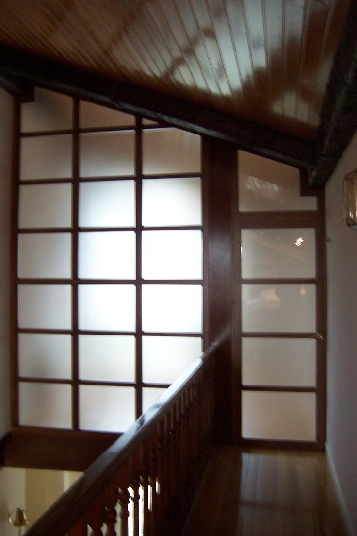 Cerramiento en madera y cristal al ácido en zona abuhardillada, con puerta de entrada abatible. Igualado en tinte al color original de la escalera.