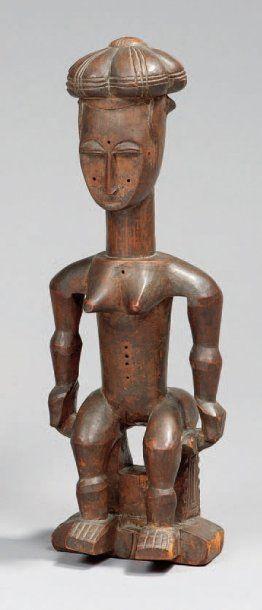 Statuette Atié Côte d'Ivoire Bois Hauteur : 29 cm Belle et ancienne statuette représentant un personnage féminin assis sur un tabouret de type Akan. Les volumes sont bien dessinés, la coiffure est composée de cinq chignons. Traces de chevilles aujourd'hui disparues. Légères fentes. Pied cassé et recollé.