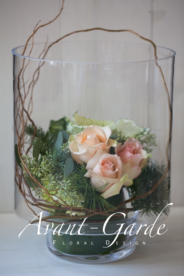 touches of curly willow and blooms with succulents in bubble bowl.