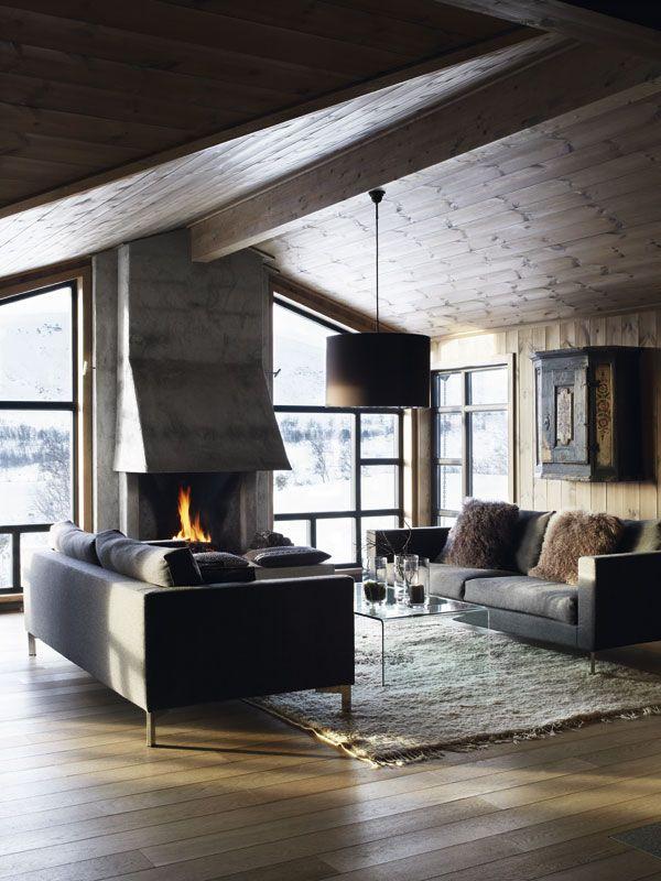 pStramme, tidløse sofaer skaper et moderne preg i rommet – og danner en ren, fin kontrast til bondeantikvitetene. Herfra kan man virkelig nyte både utsikten, eventyrlige solnedganger og peisbålet! (Sofaer fra J.Eilersen, bord fra Tanum Møbler, lampe fra Luceplan)./p