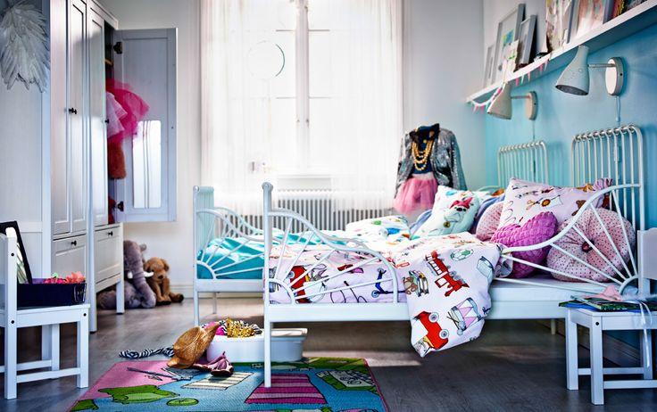 Een kinderkamer met twee witte bedden, een met lichtroze beddengoed en de andere met lichtblauw.
