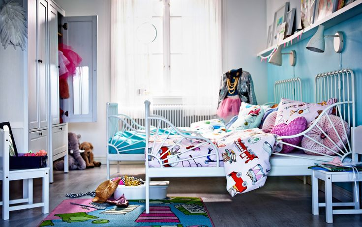 A children's room with two white beds, one with light pink bed linen and the other with light blue.