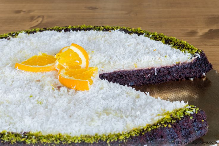 Sliced delicious chocolate cake with coconuts and orange slices on topping