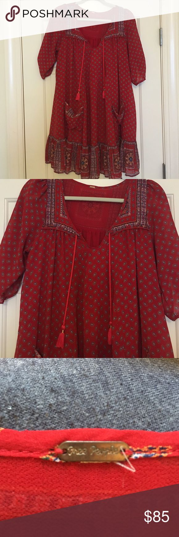 Free people red tunic dress! Free People, red tunic dress with tassels and pockets. Never worn. Free People Dresses Long Sleeve