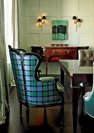 Personality filled Chicago dining room by summer Thornton featuring pale green paneling, antique sideboard, velvet tufted sidecars, and a fabulous taffeta tartan wing armchair at the head of the table.
